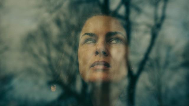 Spiegelung einer Frau in einem Fenster, im Hintergrund Bäume